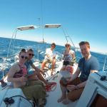 Young group of tourist drinking and having a good time on a sailboat